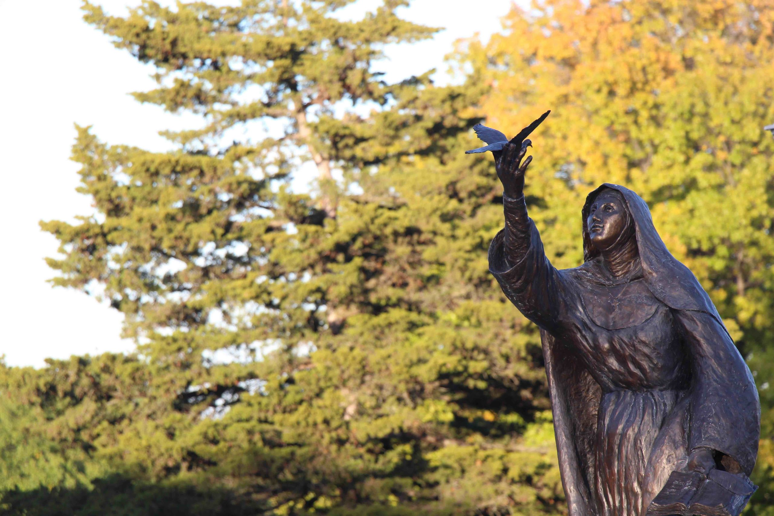The statue of St. Teresa of Avila with fall foliage in the background.