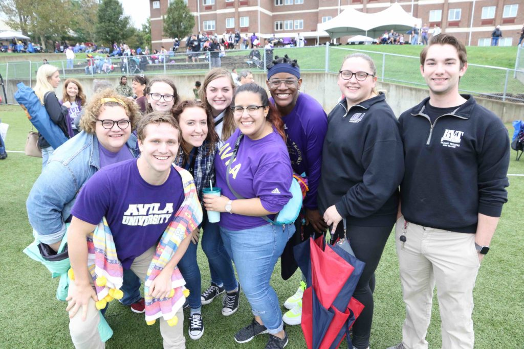 A group of students pose for the camera while standing on the football sidelines