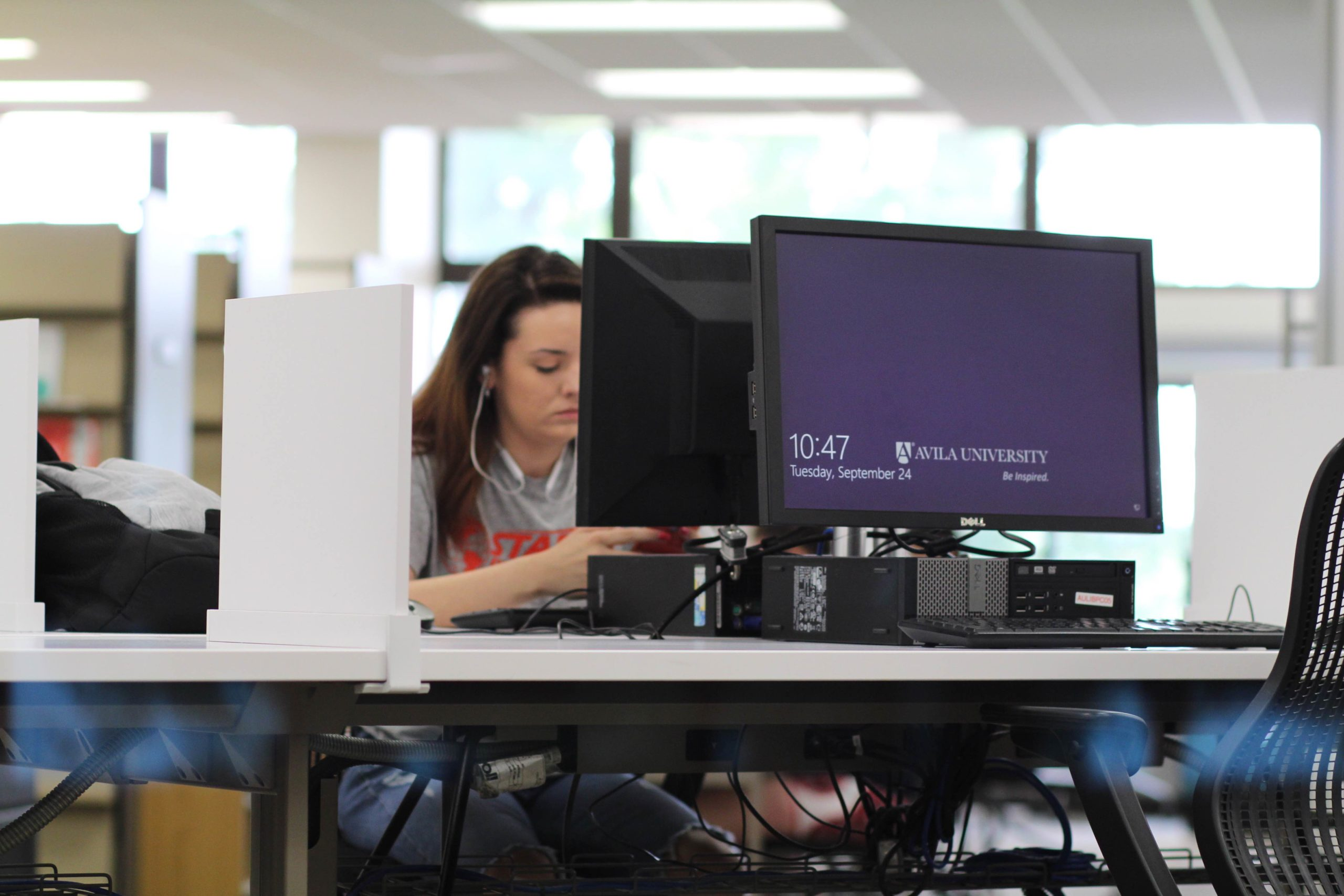 A student works at a computer station in the Learning Commons