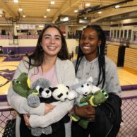 Two students pose with their arms filled with stuffed animals inside Mabee Fieldhouse