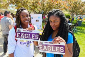 "Two students proudly holding up the personalized license plates they created at a campus carnival. Both license plates say ""Eagles"""
