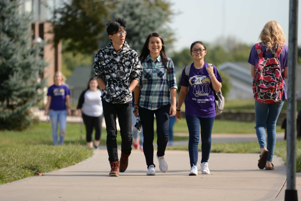 A group of three international students walk along the campus sidewalks