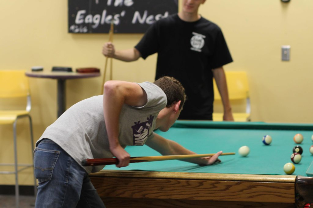 Two students playing pool in the Eagles Nest