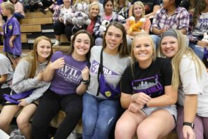 A group of five students pose on the bleachers inside Mabee Fieldhouse