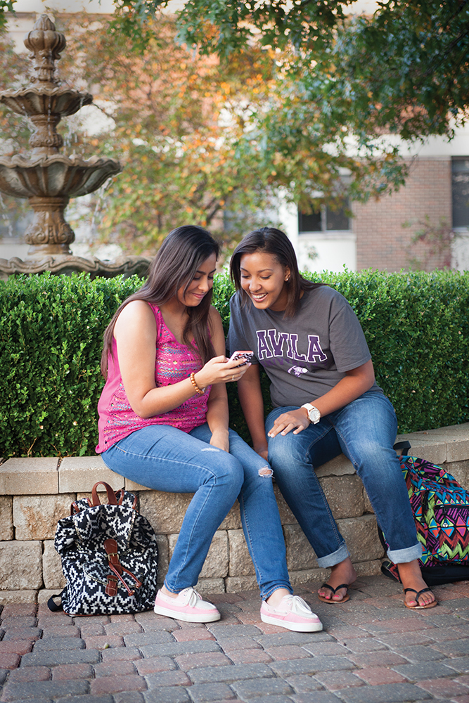 Two students sit on the fountain wall looking at a cell phone