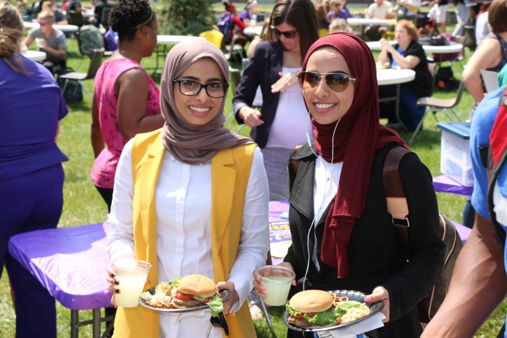 Two students enjoying the free burgers at a campus carnival