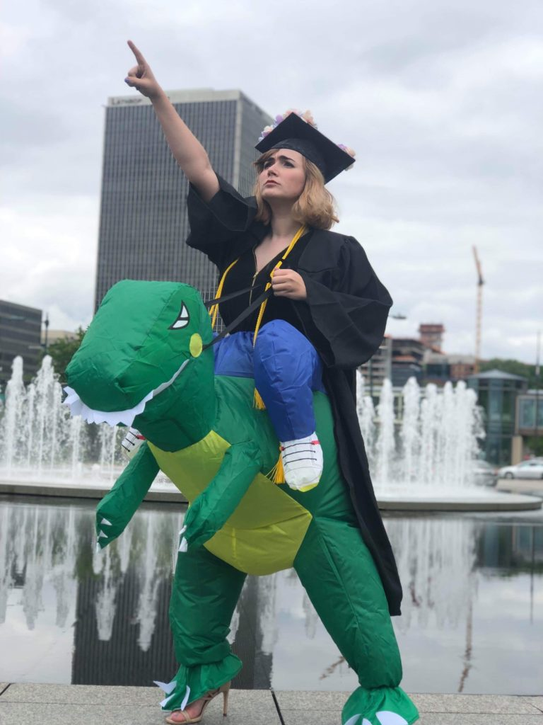 Student in cap and gown wearing a T-Rex costume