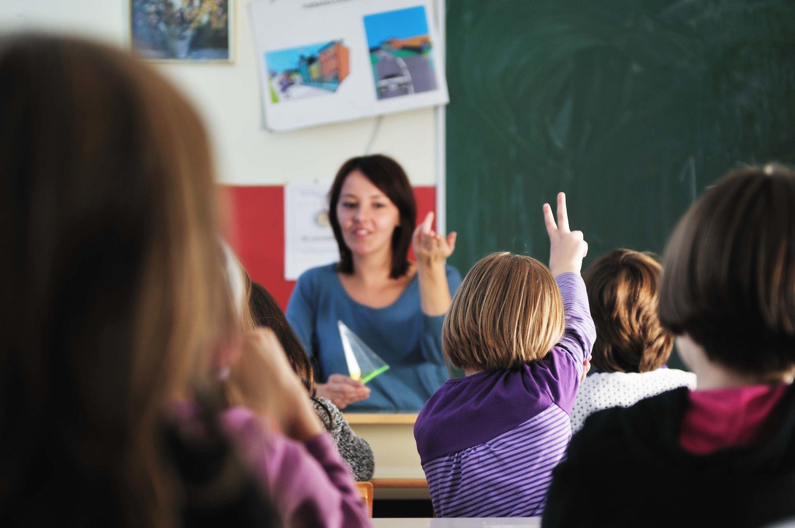 Elementary school teacher sitting at her desk calling on a young student who has her hand raised.