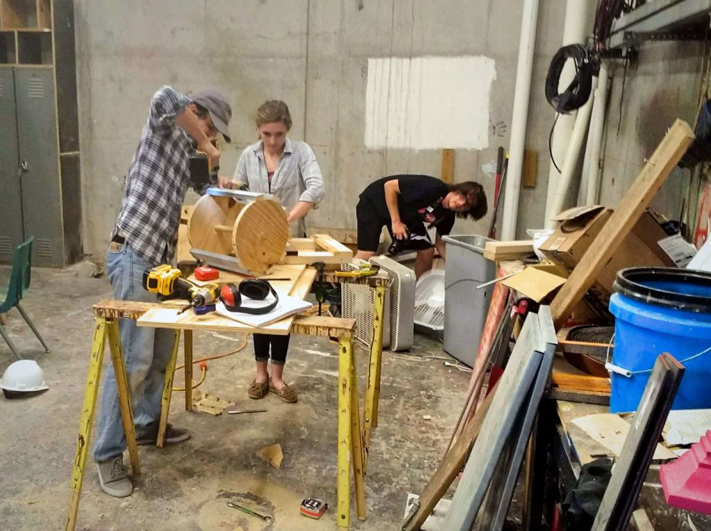 Three students working inside the scene shop