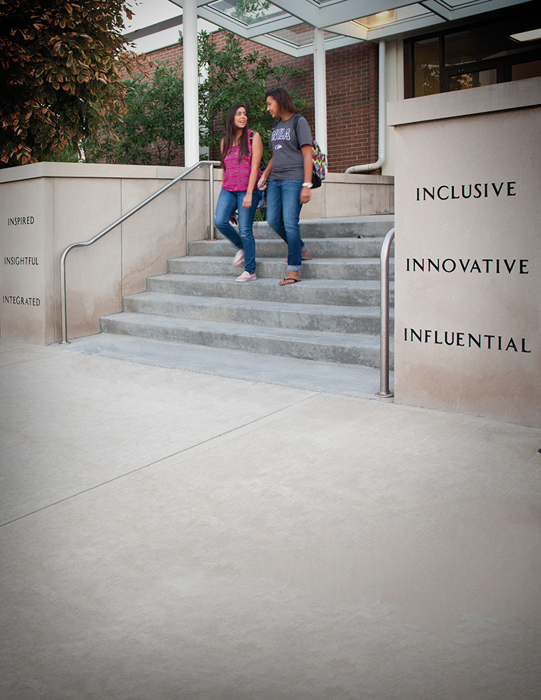 "Two students walking down the steps in front of Blasco Hall. Inscriptions on the stairs say, ""Inspired. Insightful. Integrated. Inclusive. Innovative. Influential."""