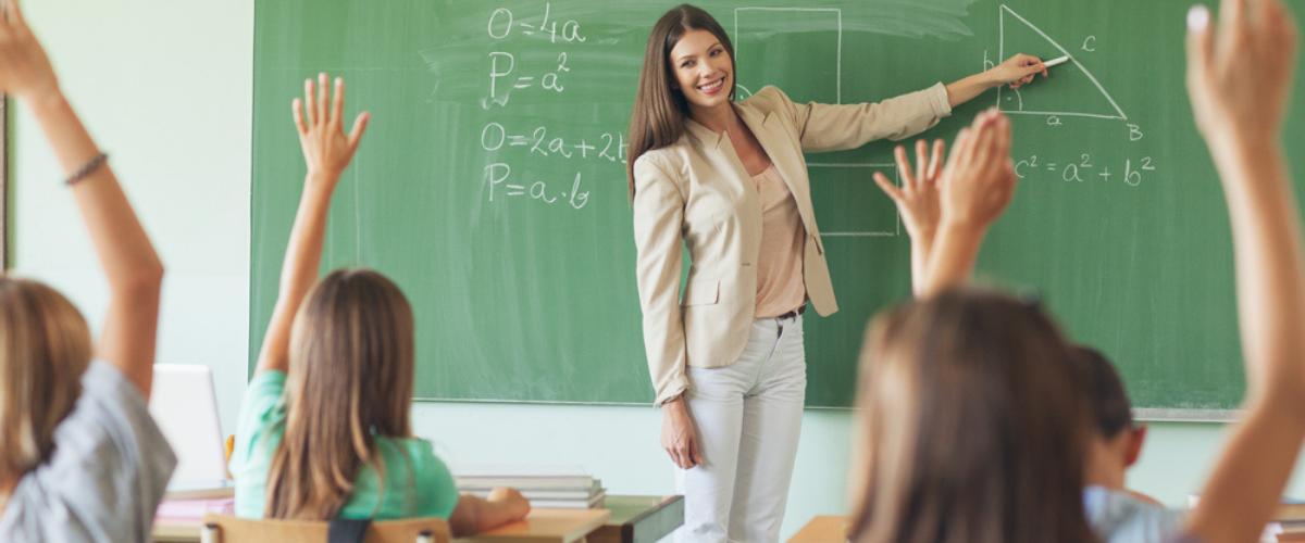 Female teacher in front of classroom pointing to chalkboard