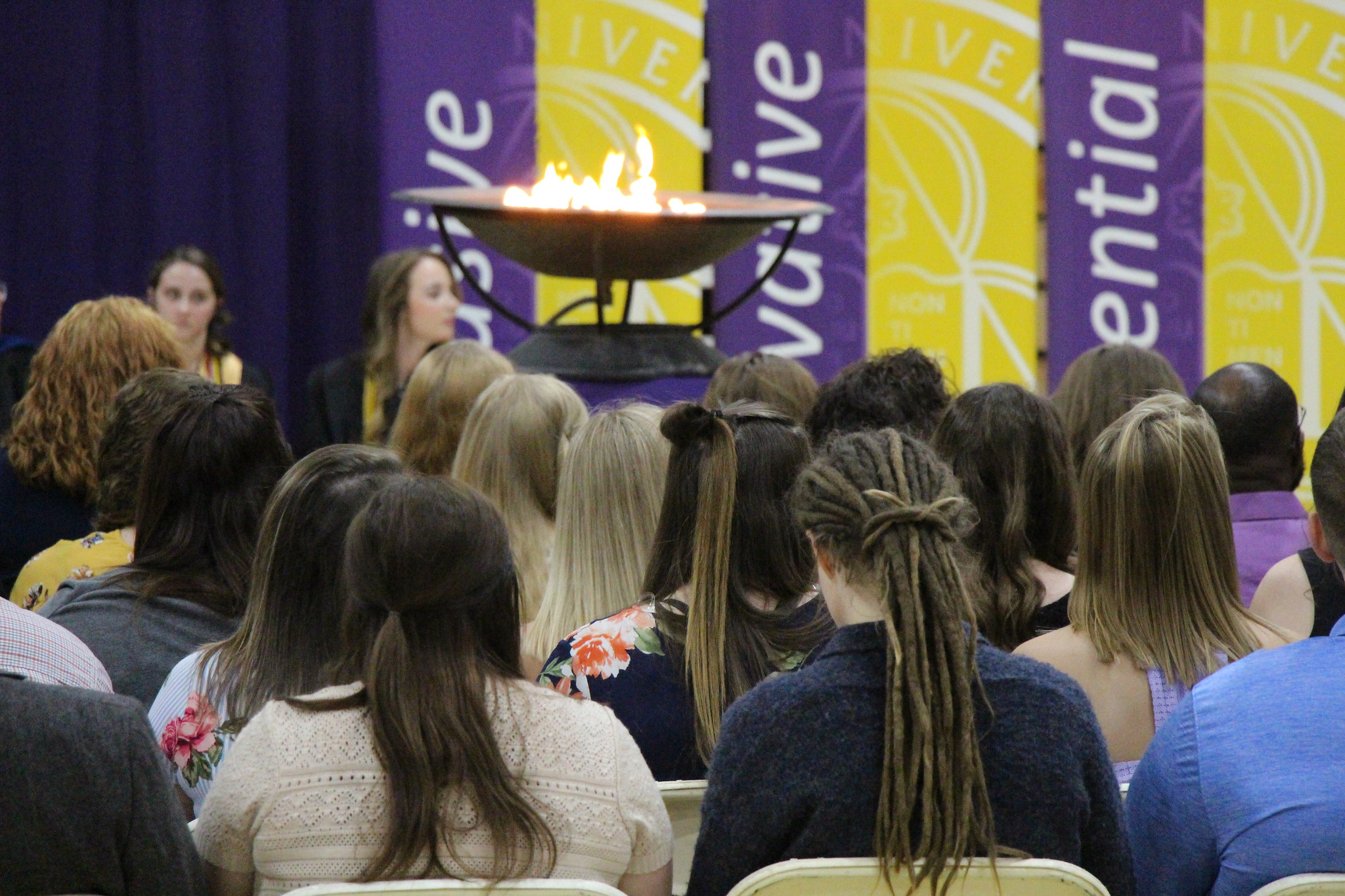 Image of students in audience with Avila flame in the background