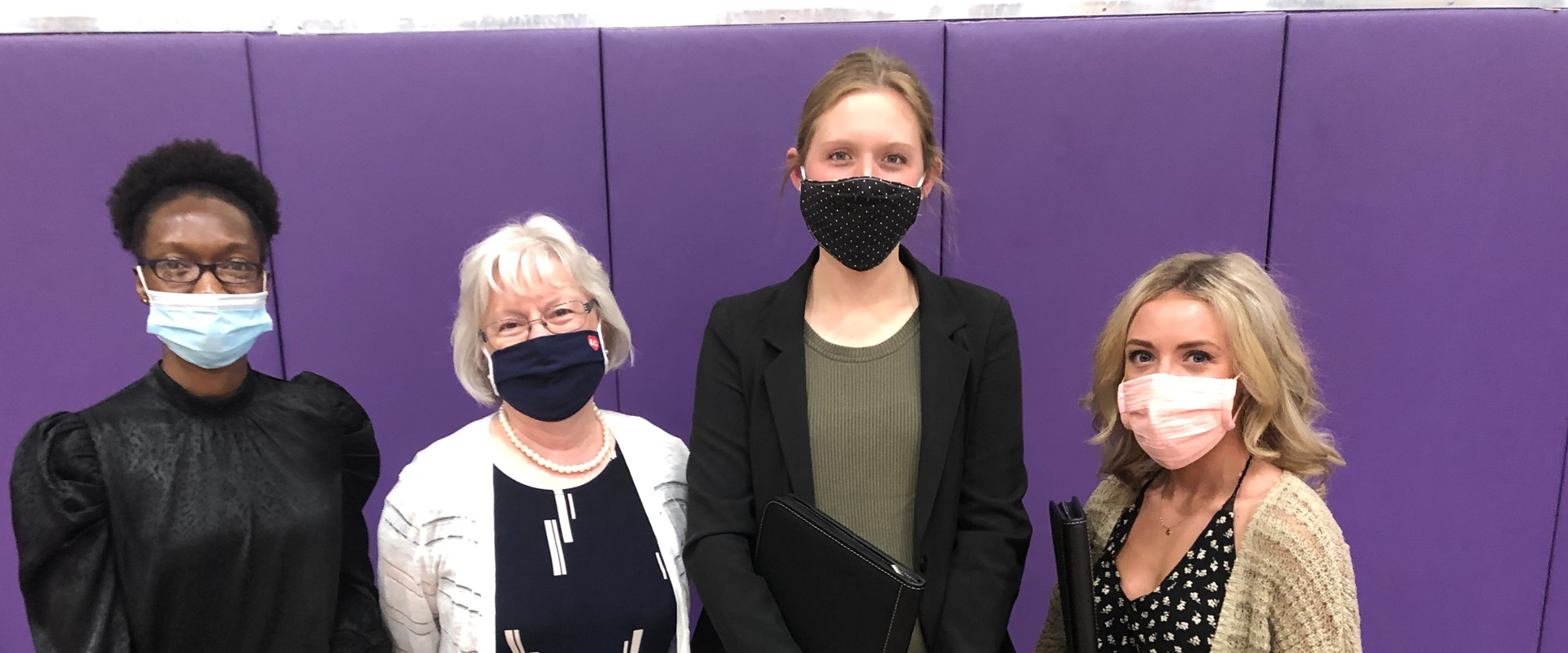 Four women posed in-line with masks on
