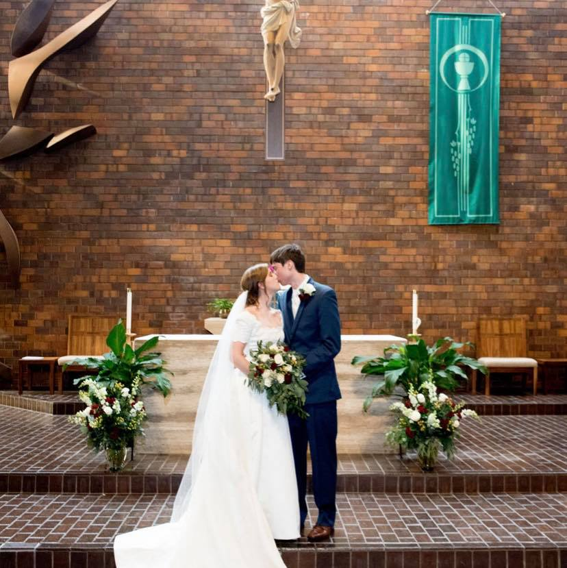 Photo of bride and groom kissing at altar