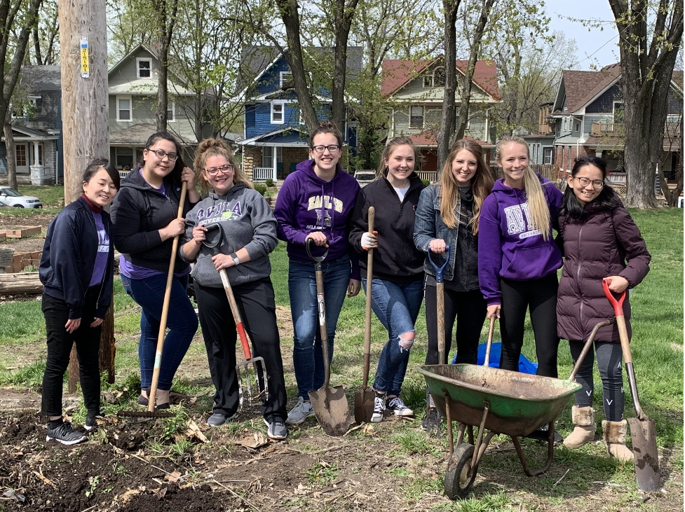 Eight students with shovels, rakes, forks, and wheelbarrow gardening at St. James