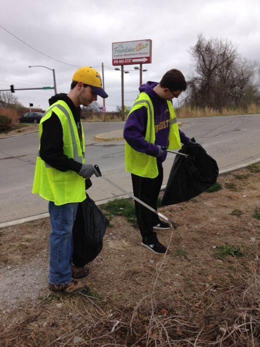 Two students picking up trash along the roadside