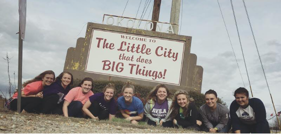 """Group of students posing in front of """"Welcome to the little city that does big things"""" sign"""