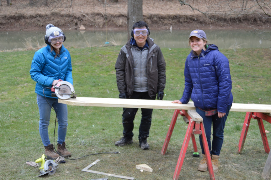 Three students with lumber, saw horses and hand saw