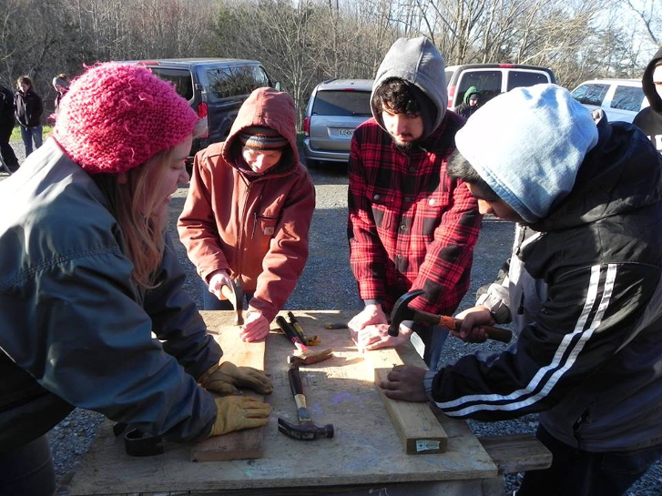 Four students using construction tools