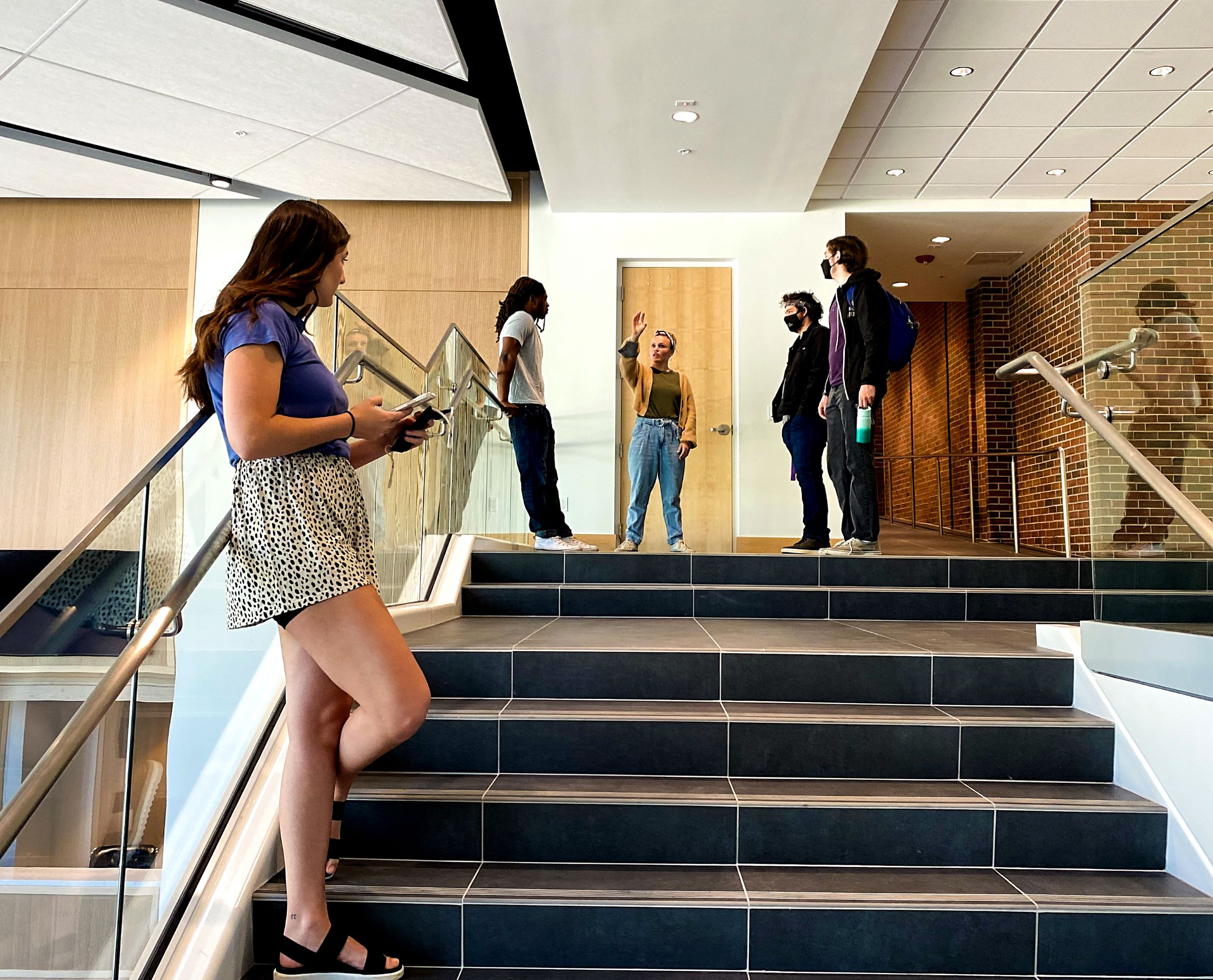 Students in conversation on the stairs of the GPAC grand lobby