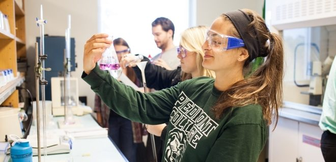 Student looking at beaker in lab