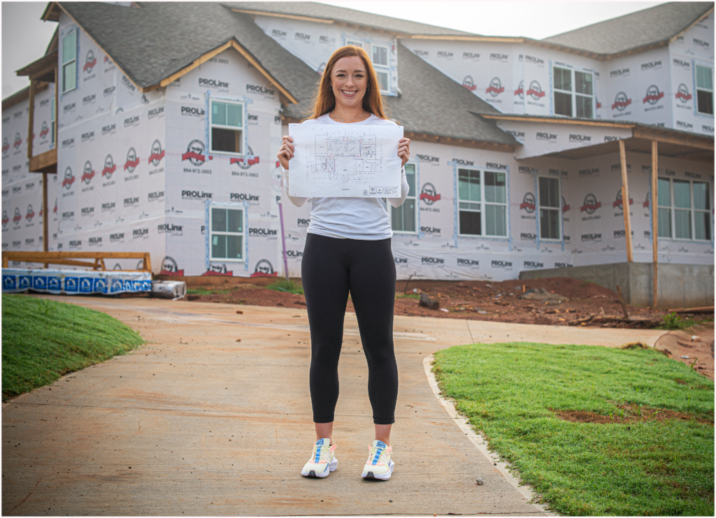 Mackenzie Wilcox graduated with her master's degree in Health & Human Performance in July and is now designing a new fitness center. Here, she holds blueprints of the fitness center, which is currently under construction.
